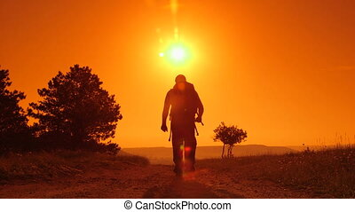 Hiker on the trail at sunset, lifting hands