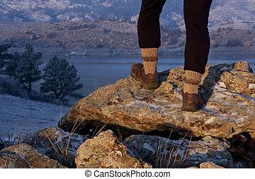 hiker or trail runner legs on rock in sunrise light