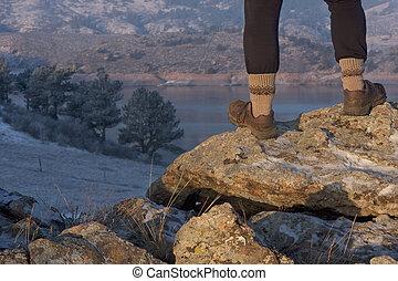 hiker or trail runner legs on rock overlooking mountain lake