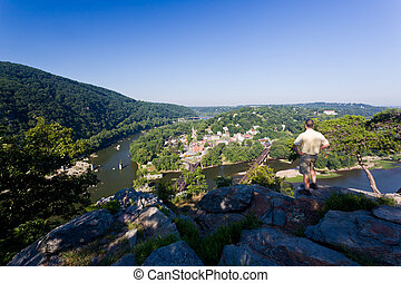 Senior male hiker overlooking the shenandoah and potomac rivers by the town of Harpers Ferry