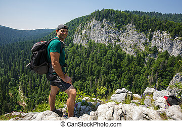Hiker posing on a very high cliff