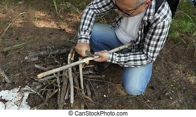 Hiker prepares wood splinters for fire