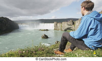 Hiker relaxing hiking - waterfall Godafoss Iceland. Man hiker resting on travel visiting tourist attractions and landmarks in Icelandic nature on Ring Road, Route 1.