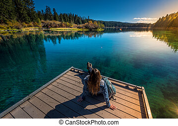 Hiker resting on a deck by the Clear Lake Oregon