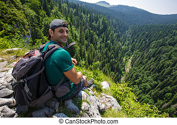 Hiker resting on a very high cliff