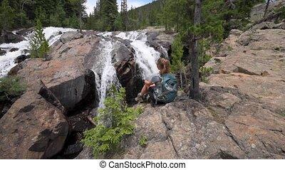 Hiker rests near  Jasper Creek Falls Colorado Indian Peaks Wilderness
