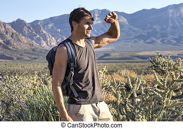 Hiker shields eyes from sun in desert