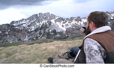 Hiker sits and drinks hot tea from a thermos and enjoys a...