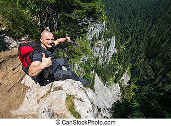 Hiker sitting on the edge of a very high cliff