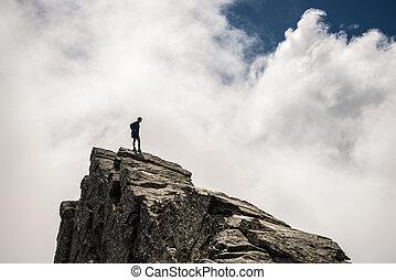 Hiker standing high up on rocky mountain peak - Hiker ...