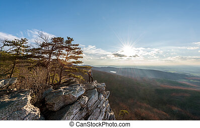 Hiker standng at the summit of an Appalachian mountain at edge of cliff looking at the vista