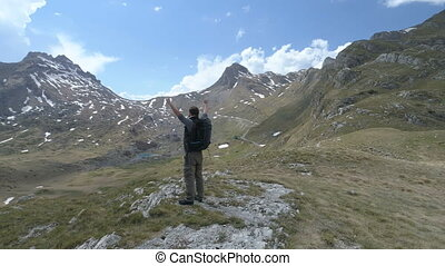 Hiker stands on top and keeps his hands raised in a gesture...