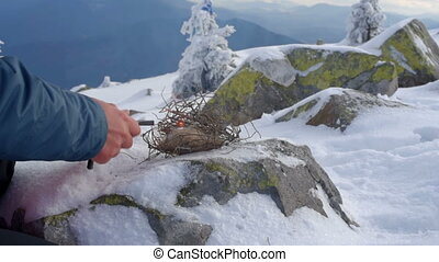 Hiker starts fire in the snowy mountains. hiker is warming...