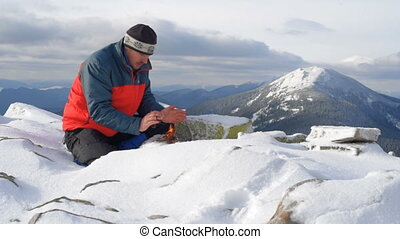 hiker is warming up by the fire - Hiker starts fire in the...