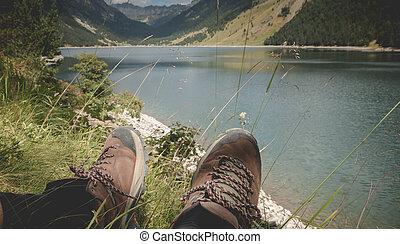 hiker taking a break sitting near the lake of Oule in Pyrenees, France