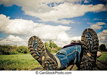 hiker taking a rest on a summer-day. Focus on bottom of hiking-boots .personal editing velviafilter