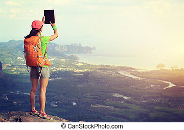 hiker taking photo with digital tablet at seaside mountain cliff