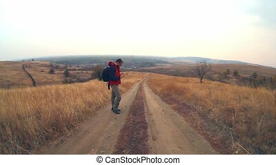 hiker traveler man with backpack in the autumn is on way to nature is solitary tree travel