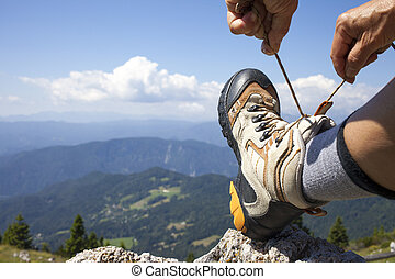 Hiker tying boot laces