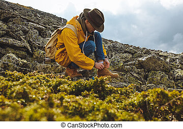 Hiker tying boot laces on the mountain