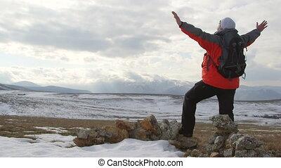 Hiker walking away through the snowy mountain plateau