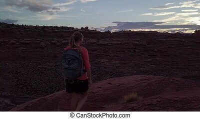 Hiker walks up to the edge of the Canyon Needles District of...
