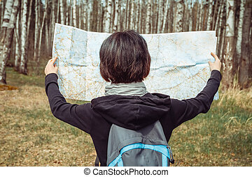 Hiker with a map in the forest