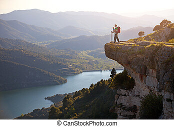 Hiker with baby standing on cliff and enjoying valley view