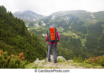 Hiker with backpack and trekking sticks on top of mountain admiring the view
