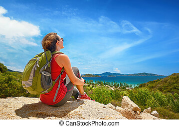 Hiker with backpack relaxing on top of the mountain and enjoying beatiful coast view.