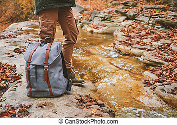 Hiker with backpack standing near a river - Unrecognizable...