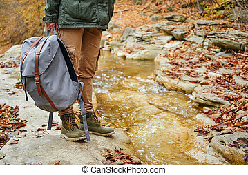 Hiker with backpack standing near a stream