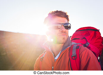 Hiker with backpack standing on mountain top enjoying the view