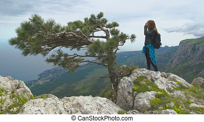 Hiker with backpack standing on top of the mountain and enjoying valley view.