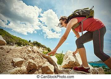 Hiker with backpack walking on seaside trail looking at beautiful landscape motivation and inspiration.