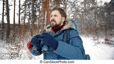 Hiker with binoculars in forest