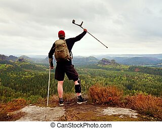 Hiker with broken leg in immobilizer. Tourist with medicine crutch above head achieved peak.