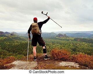 Hiker with broken leg in immobilizer. Tourist with medicine crutch above head achieved peak.