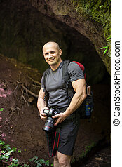 Hiker with camera near a cave