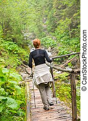 Hiker with hiking poles looking walking over wooden bridge in a forest