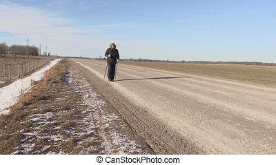 Hiker with hiking poles walking near highway