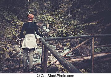 Hiker with hiking poles walking over wooden bridge in a forest