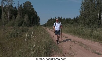 Hiker with hiking sticks at side of rural road