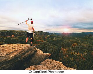 Hiker with knee joint bandage and forearm poles. Hiker on...