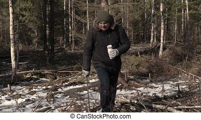 Hiker with machete and thermos in forest