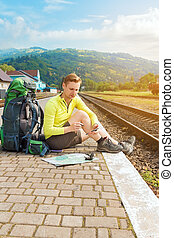 hiker with smartphone at train station