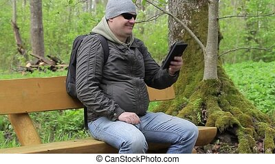 Hiker with tablet PC in park
