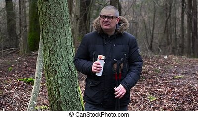 Hiker with thermos near tree in the park