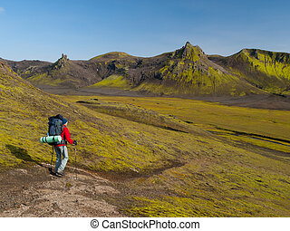 Hiker with trekking poles on Laugavegur trek, Iceland