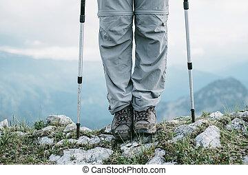 Hiker with trekking poles outdoor.